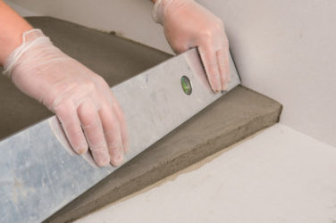 Как выровнять стяжку плиточным клеем?